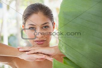 Beautiful brunette smiling at camera behind leaf