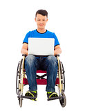 happy young man sitting on a wheelchair with a laptop