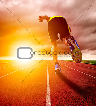 Athletic young man running on race track with sunset background