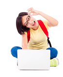 happy young student girl sitting on floor  with a laptop