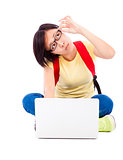 doubted young student girl sitting on floor with a laptop
