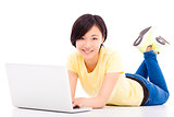 smiling young girl lying on the floor with a laptop