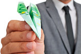 businessman with a paper plane made with a 100 euro banknote
