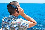 young man listening to music with headphones in front of the sea