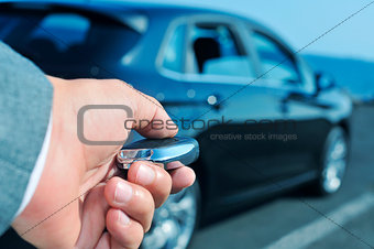man in suit opening his car with the control remote key
