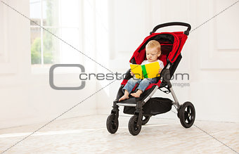 Toddler boy sitting in stroller at home and looking at open book