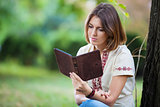 Young attractive woman reading e-book in summer park
