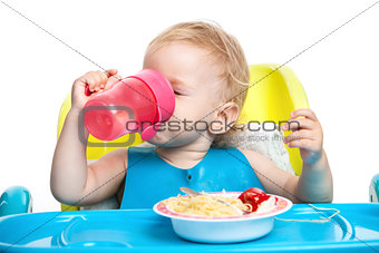 Little boy drinking water while sitting at table with plate of spaghetti