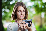 Young woman looking at screen of retro style camera and smiling