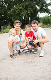 Young family with two boys playing with RC quadrocopter toy