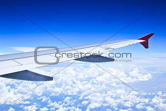Airplane wings in the blue clouds.
