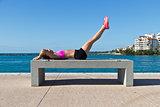 Hispanic woman doing leg raises for fitness