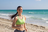 Hispanic woman running on the beach