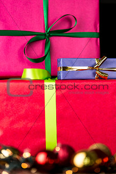 Three wrapped gifts, bowknots, spheres and glitters
