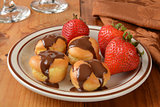 Cream puffs with chocolate and strawberries