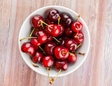 White bowl of cherries on wood