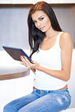 Beautiful woman relaxing at home with a tablet-pc