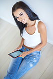 Smiling woman sitting on a floor with a tablet-pc