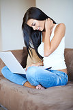 Young woman smiling as she browses on a laptop