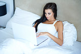 Beautiful woman working in bed