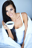 Beautiful rejuvenated young woman drinking coffee