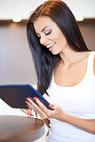 Happy young woman surfing on a tablet-pc