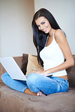 Beautiful casual young woman using a laptop