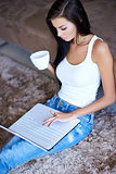 Woman relaxing with coffee and her laptop
