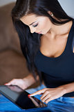 Tanned young woman using a tablet computer