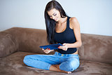 Young woman sitting on a sofa with her tablet