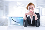 Composite image of redhead businesswoman sitting at desk