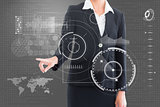 Composite image of businesswoman pointing at interface
