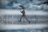 Composite image of businessman jumping holding an umbrella on tightrope