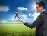 Composite image of businessman holding business man jumping