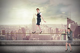 Young businesswoman pulling a tightrope for business woman