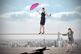 Young business woman pulling a tightrope for businesswoman