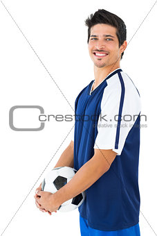 Football player in blue holding ball