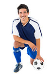 Football player in blue kneeling with ball