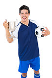 Football player in blue holding winners cup and ball