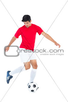 Football player in red kicking ball