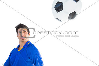 Football player in blue jumping to ball
