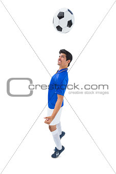 Football player in blue heading ball