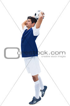 Football player in white throwing ball