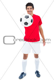 Football player in red showing ball