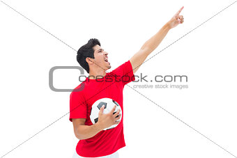 Football player in red holding ball and pointing