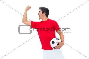 Football player in red holding ball and cheering