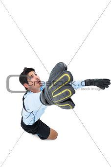 Goalkeeper in blue making a save