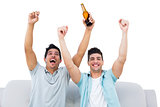 Happy football fans cheering together with beers