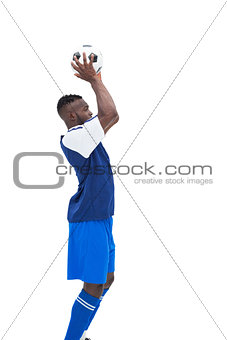 Football player in blue throwing ball