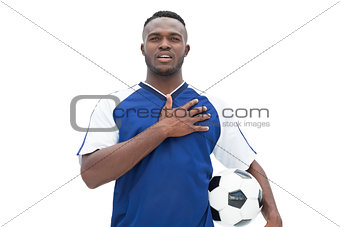 Football player in blue standing with the ball listening to anthem